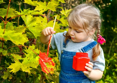 little girl paint colors on the leaves of the tree Stock Photo