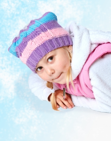 portrait of a little girl wearing winter clothes, christmas, lying on the floor