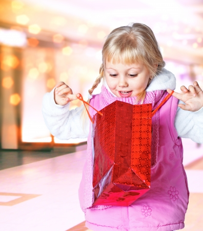 portrait of a little girl holding a bag of shopping, shop, gift  Stock Photo
