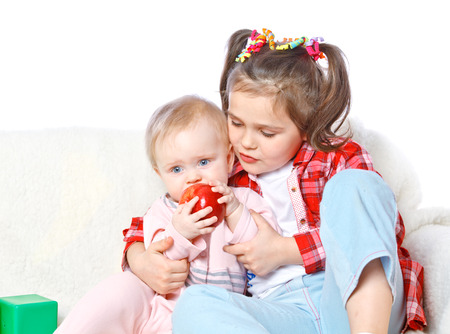 portrait of a big sister feeds the younger apple, fruit, health, love