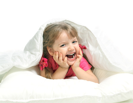 Portrait of a little girl lying in bed, gay, white background Stock Photo - 24913261
