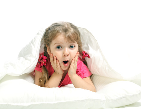 Portrait of a little girl lying in bed, gay, white background Stock Photo - 24913264