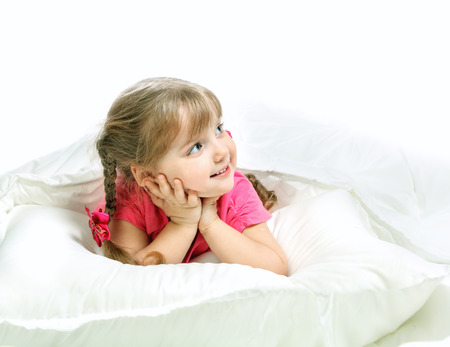 Portrait of a little girl lying in bed, gay, white background