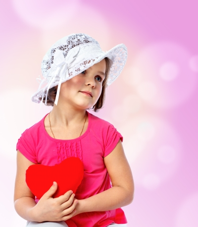 little girl holding two hearts on the abstract background