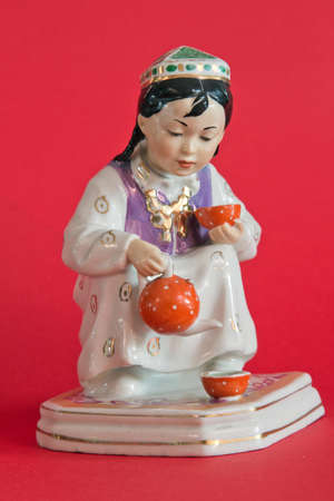 faience: Girl pouring tea, faience statuette Stock Photo
