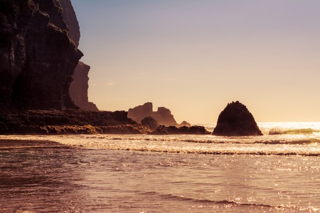 Retro style photo of a beautiful summer day at Piha Beach, New Zealand. Sunlight sparkles all over the waves, rock formations partially hidden in the foam. Sepia toned