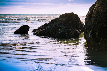 Setting sun backlight srock formations in shallow water at the beach. Mirror-like water surface, distance waves rushing toward the shore