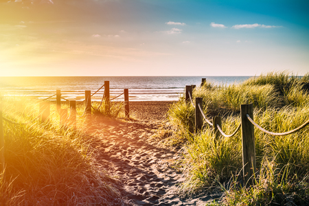 Golden sunset over sandy pathway with grass reeds and wooden posts on each side leading to a beautiful sea bay