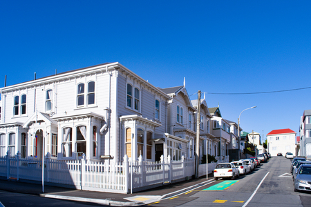 A row of traditinal white villas in a steep street of quiet suburb in Wellington, New Zealand.