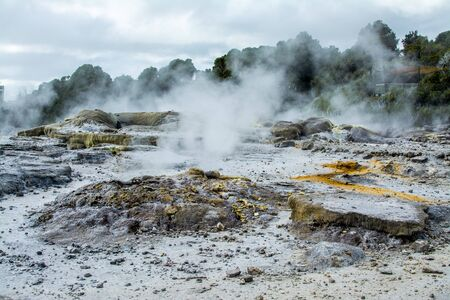Steam rising above rocky geothermal area near Rotorua, New Zealand. Sulphur springs field and steam pools with boiling mud. Banco de Imagens