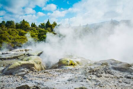 Steam rising above sulphur covered rocks in a geothermal area near Rotorua, New Zealand.