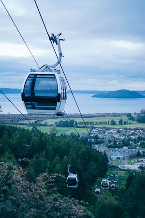 A line of gondolas going up and down above green slopes. Cableway in the mountains near Rotorua, New Zealand Archivio Fotografico