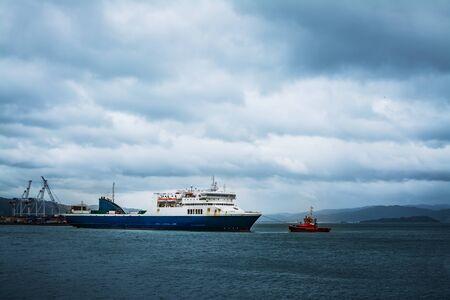 Jaskrawoczerwony holownik ciągnący duży prom międzywyspowy z Wellington Port w sztormowy zimowy dzień