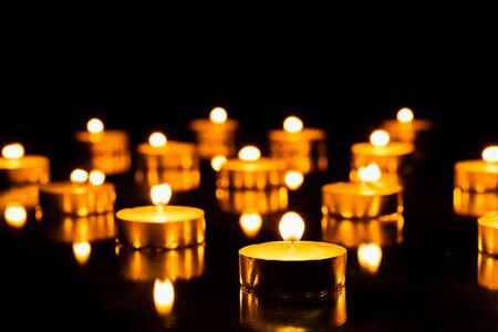 Grupo de velas de té encendidas sobre fondo de espejo negro. Enfoque selectivo