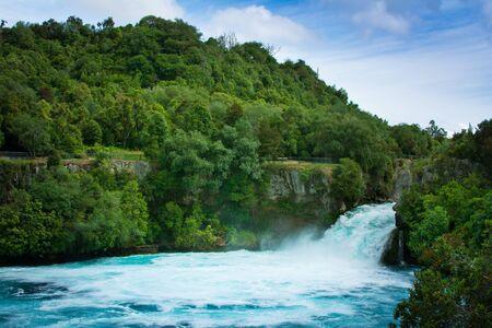 Panoramic view over Huka Falls and a pool beneath amongst lush green trees covered rocks. Waikato river. Taupo, New Zealand