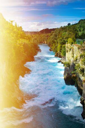 Eveniing sun glowing over churning waters of Huka Falls. Waikato river. Taupo, New Zealand