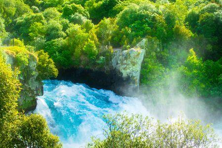 Full power of Huka Falls rushing down amongst rocks and trees. Waikato river. Taupo, New Zealand