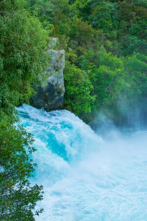 Huka Falls rushing down amongst rocks and trees. Waikato river. Taupo, New Zealand 版權商用圖片