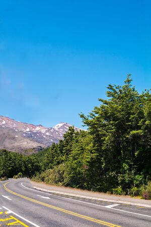 A curve of mountain highway with snow-covered summit Mt Ruapehu in the distance