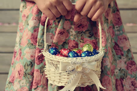 Retro style photo of girls hands holding a a small basket full of colourful Easter eggs