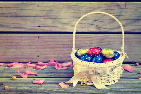 Retro style photo of a small basket full of colourful Easter eggs on a wooden background Stock fotó