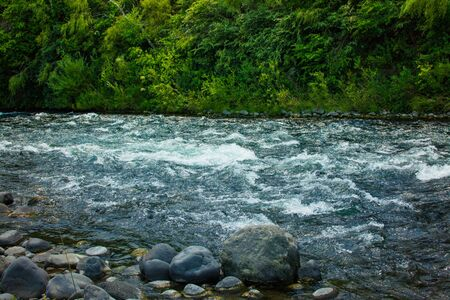 Water churning over the rocks in the shallows of Tongariro River. Turangi, New Zealand