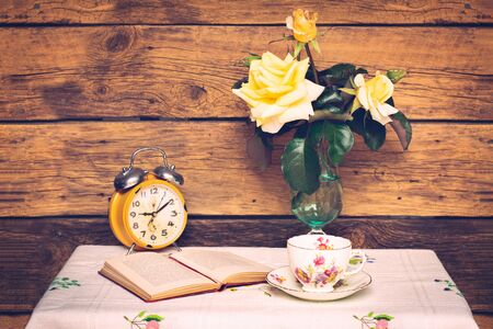 Vintage photo of embroidered tablecloth covered table with a cup of tea, an open book, an alarm clock, and flowers against wooden background