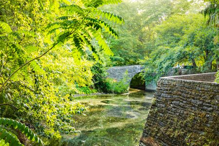 Sunset light pouring over stone arched footbridge running under mature trees