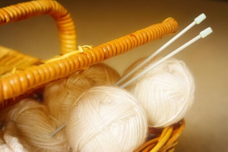 Close up of ivory wool yarn and knitting needles in a woven basket with a lid. Selective focus