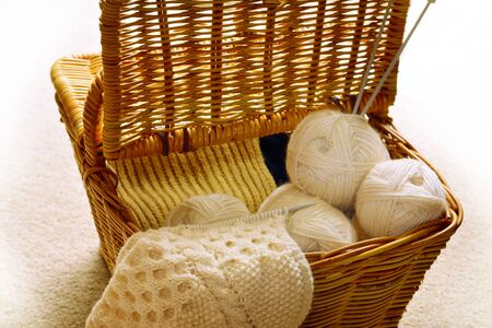 A wicker basket with ivory wool yarn, knitting needles and knitwork in progress. Selective focus Archivio Fotografico