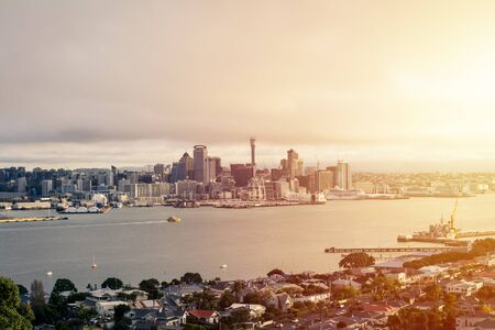 Auckland City downtown skyline partially obscured by low clouds in sunser light. View from North Shore