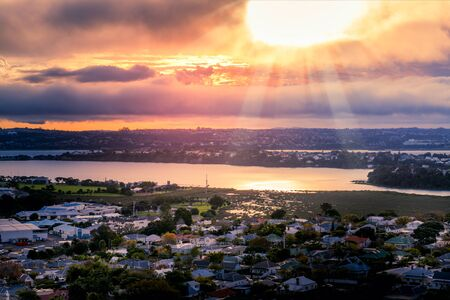 Setting sun breaking through flaming clouds over Auckland Harbour and suburb of Devonport. Auckland, New Zealand