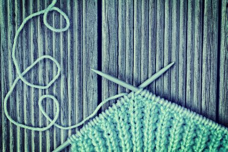 Vintage photo of knitting needles crossed over knitwork in progress and looping yarn thread on wooden background. Selective focus. Toned image