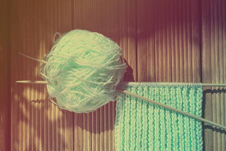 Retro-style photo of a blue yarnroll, knitting needles, and knitwork in progress on wooden background. Toned image. Selective focus