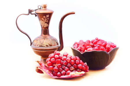 Traditional ottoman ewer and open ripe pomegranate in front of a bowl full of pomegranate seeds. Isolated on white 版權商用圖片