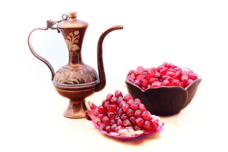 Stilllife with traditional ottoman ewer, open ripe pomegranate and a bowl of pomegranate seeds. Isolated on white