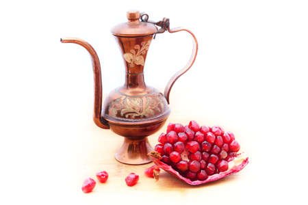 Bulbous ottoman ewer and a portion of ripe pomegranate. Concept of Middle East. Isolated on white 版權商用圖片