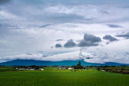 A glimpse of Mount Taranaki through heavy clouds on gloomy winter day. Imagens