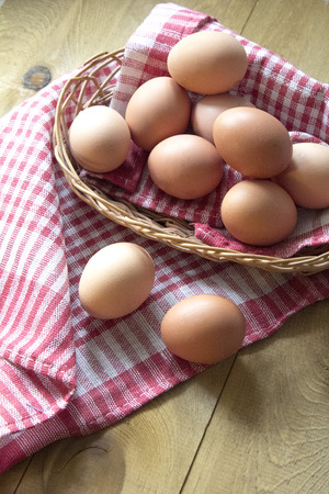 Many brown raw eggs are in a wicker basket on the table