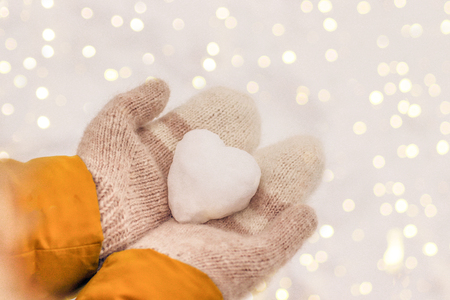 Hands in warm knit mittens with a snowy heart on a background of snow, Valentine's Day romantic concept Foto de archivo