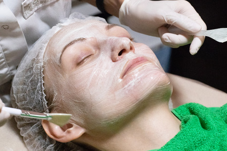 Woman getting facial care by beautician at spa salon, side view, close-up.  Face skin care.