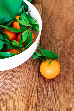 Fresh juicy clementine mandarins with green leaves in a basket on a brown wooden table
