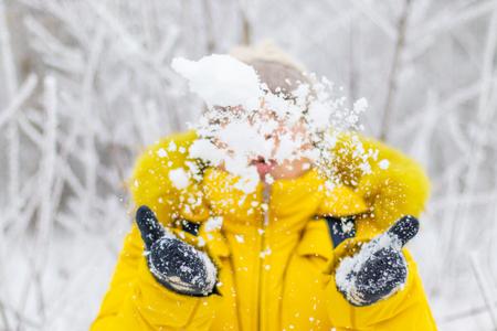 Happy woman in yellow winter clothes throw snow Standard-Bild - 116378983