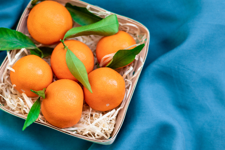 Fresh juicy clementine mandarins with green leaves in a basket on blue background
