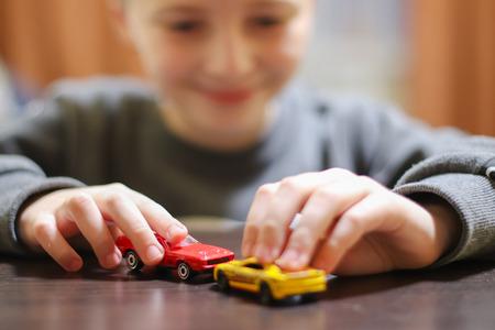 Gelukkig kind 6-8 jaar spelen met auto's en speelgoed thuis, binnen. Stockfoto