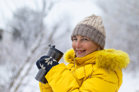 Adult woman in yellow winter jacket, beige hat and blue mittens enjoying coffee on a winter day. Close-up with space for text