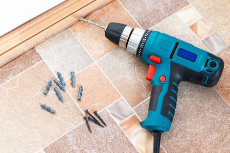 Elektrische Bohrmaschine und Nägel auf Holzboden hautnah. Installation von Bodensockel aus Kunststoff.