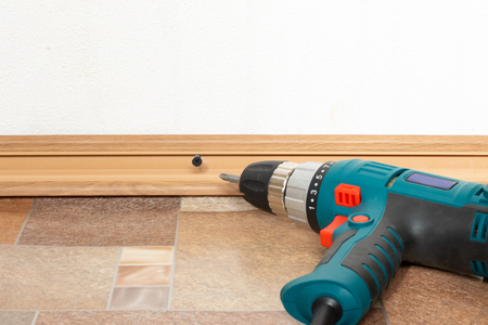 Installation of plastic floor plinth heavy screwdriver lying next to the screw on the wooden floor