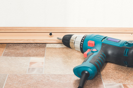 Close up electric drill and nails left on wooden floor. Installation of plastic floor plinth.