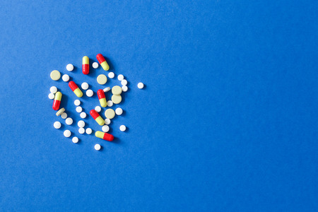 Scattered color pills isolated on blue background with copy space for your text. Imagens